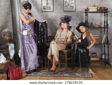 Little girls try on a dress from Grandma's chest  - stock photo