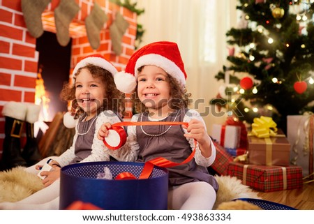 Little girls twins at Christmas sitting on the floor in Santa hats smiling and laughing in a room decorated in a happy new year.