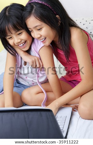 Little girls using laptop in their bedroom