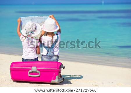 Little girls with big suitcase and map at tropical beach - stock photo