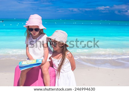 Little girls with big suitcase and map on tropical beach - stock photo