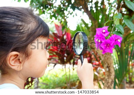 Little girls with magnifying glass at the background  - stock photo