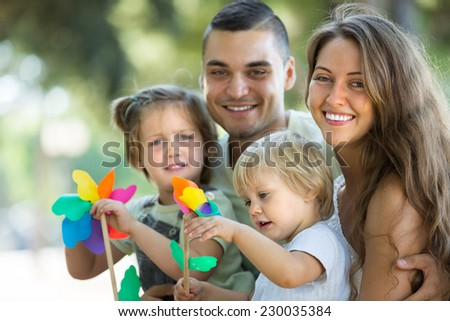 Little girls with windmills sitting on parent's arms outdoor. Focus on woman  - stock photo