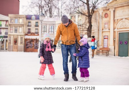 Little girls with young father enjoying skating - stock photo