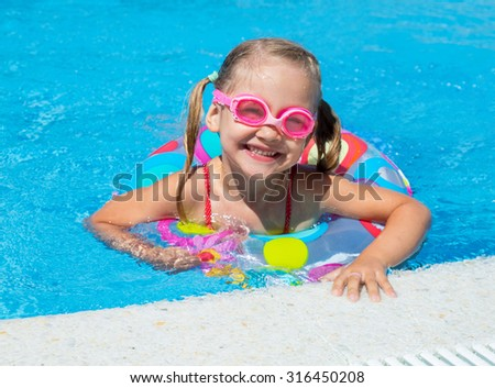 little girlswimming in the pool  in inflatable ring - stock photo