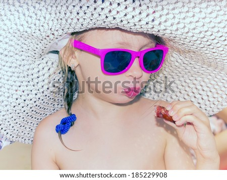 Little glamour girl in pink glasses eating sausage on the beach outdoor