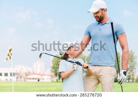 Little golfer with father. Happy young man and his son holding golf clubs and looking at each other while standing on the golf course - stock photo