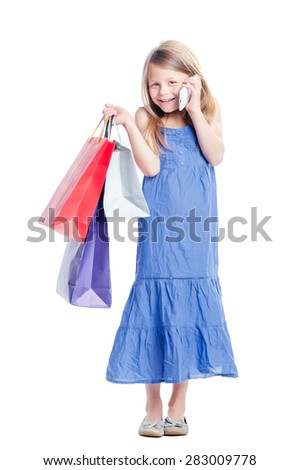 Little gossip girl. Full length of cute girl holding shopping bags and talking by smartphone. Isolated on white. - stock photo