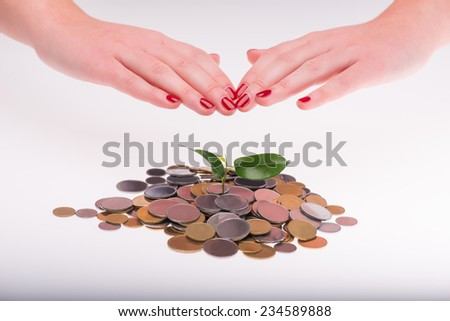 Little green plant growing in a heap of coins isolated on white background. Hands of some woman over it. Concept of new life - stock photo