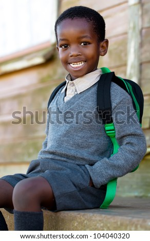 Little guy waiting for the bus, on his way to school. - stock photo