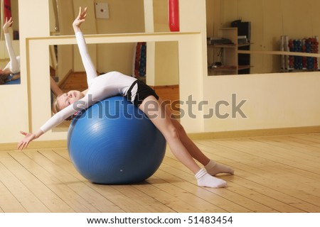 Little gymnast girl laying down on big blue ball in gym
