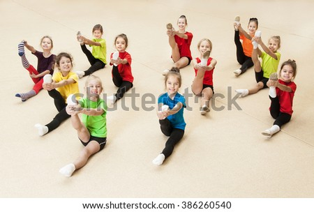 Little gymnasts doing exercises in gym