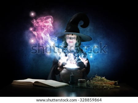 Little Halloween witch reading conjure from magic book above pot - stock photo