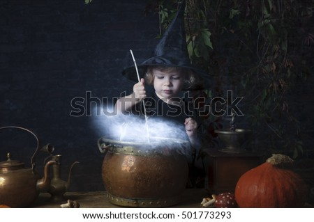 little halloween witch with boiling cauldron