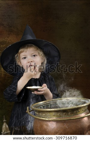 little halloween witch with cauldron in an ancient kitchen - stock photo