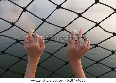 little hand holding on nylon chain link fence
