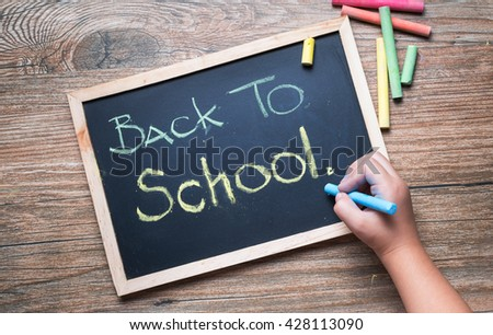 little hand writing back to school on a chalkboard - stock photo
