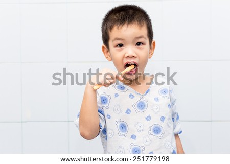 Little handsome Asian boy brushing Teeth in bath - stock photo