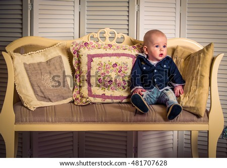 little handsome boy on the sofa, dressed in a blue shirt and denim pants, Studio shot