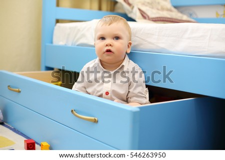 Little handsome boy sits in big blue drawer in children bedroom at home