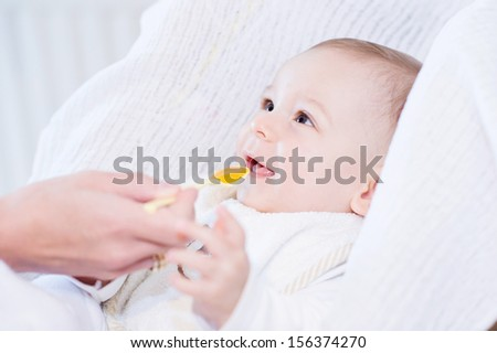 Little happy baby feeding with a spoon  - stock photo