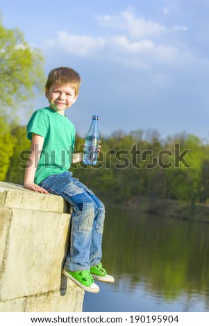 little happy boy holding a water bottle - stock photo