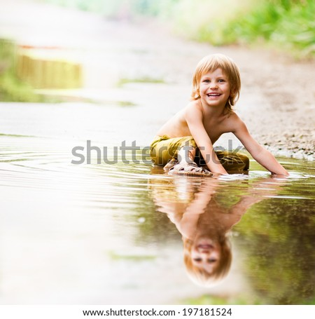 little happy boy in the puddle. summer outdoor - stock photo