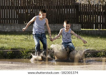 little happy boy jumping in puddle - stock photo