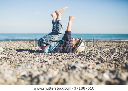 Little happy boy lying on the beach with his hands and legs up