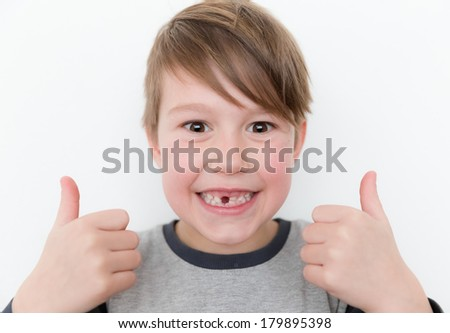 Little happy boy missing a tooth with two thumbs up - stock photo