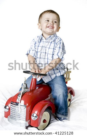 Little happy boy playing with red fire truck toy. - stock photo