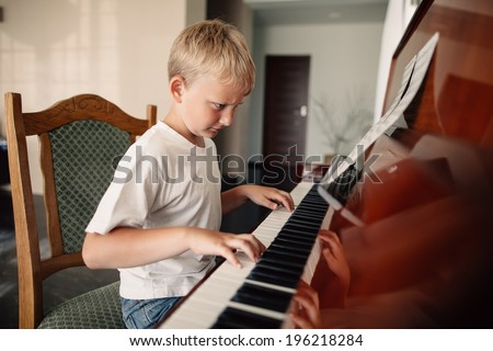 little happy boy plays piano at home - stock photo