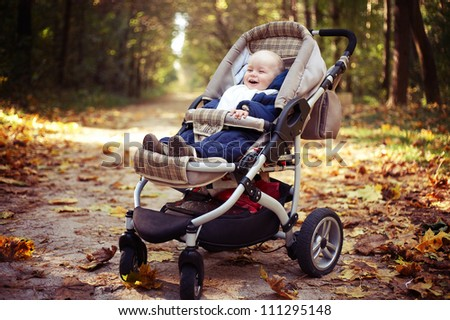 little happy boy with baby carriage in autumn park - stock photo