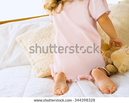 little happy cheerful girl in a white bed - stock photo