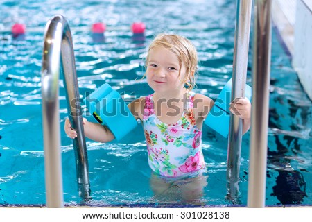 Little happy child enjoying swimming pool. Cute toddler girl wearing colorful swimsuit and armbands having fun in the water. Adorable sportsman kid promoting healthy lifestyle. - stock photo