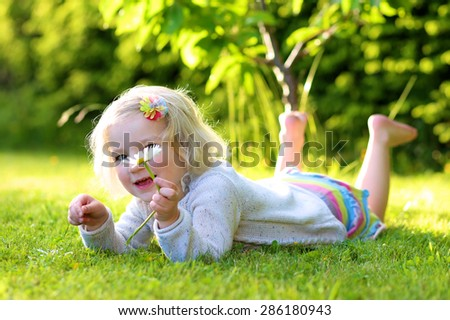 Little happy child, smiling blonde toddler girl lying on green grass holding daisy flowers playing he loves me or not