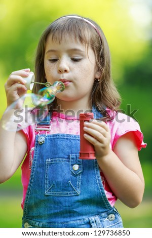 Little happy girl blowing soap bubbles in the parc