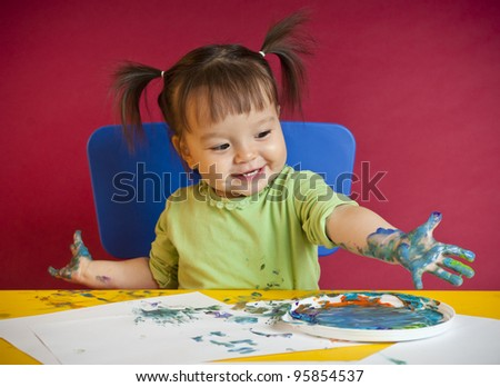 Little happy girl discovering finger painting