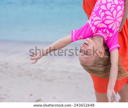 Little happy girl enjoy summer vacation with her mom at exotic beach - stock photo