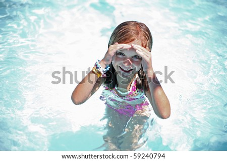 Little happy girl enjoys summer day at the swimming pool. - stock photo