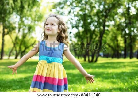 Little happy girl having fun in green summer park