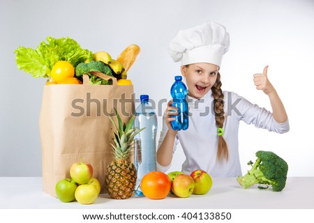 Little happy girl in a cap cook. A girl holding a bottle of pure mineral water for cooking healthy meals. A girl holds a finger up. Positive human emotion, facial expression feeling, attitude.
