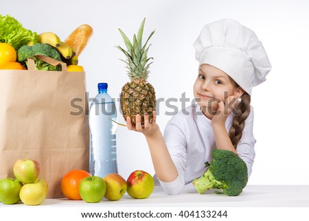 Little happy girl in a cap cook a variety of fresh food. Girl holding pineapple. and shows OK. Positive human emotion, facial expression feeling, attitude. Bag with fresh vegetables and fruits.