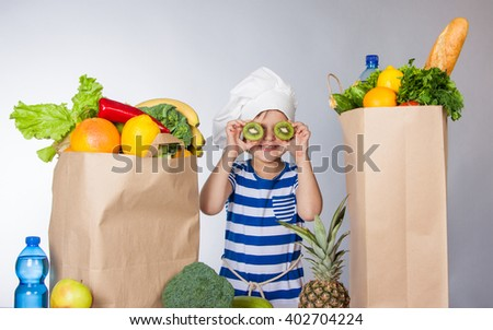 Little happy girl in chef hat with big bags of products. A variety of fresh fruits and vegetables in bags on the table. Healthy food. Child happy and healthy.