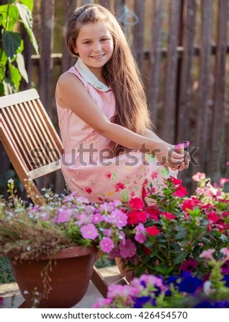 little happy girl in garden with flowers