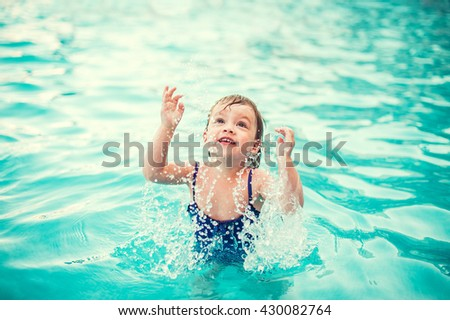 Little happy girl in swimming pool. Kid splashing on pool - stock photo