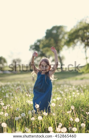 Little happy girl is playing in sunny meadow