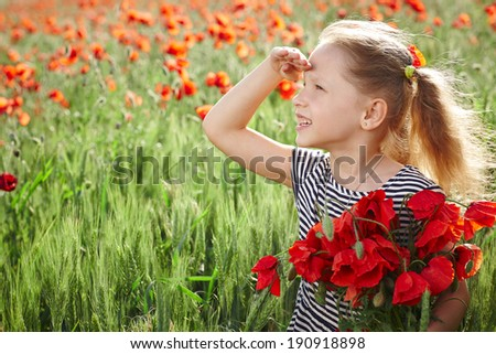 Little happy girl on the poppy meadow holding posy looking away with palm on forehead - stock photo