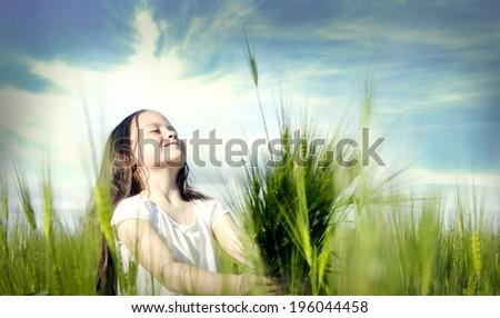 Little happy girl on wheat field - stock photo
