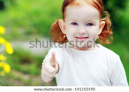 Little happy girl outdoor showing ok thumb up - stock photo